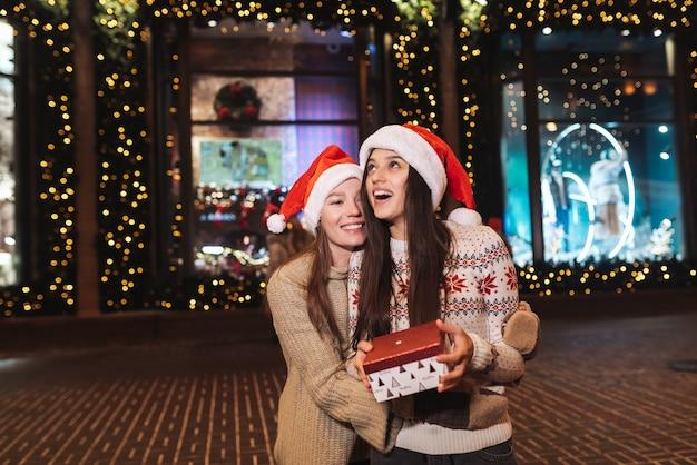 Портрет счастливых милых молодых друзей, обнимающих друг друга и улыбающихся во время прогулки в канун рождества на открытом воздухе.