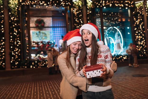 お互いに抱き合って、屋外のクリスマスイブを歩きながら笑っている幸せなかわいい若い友人の肖像画。