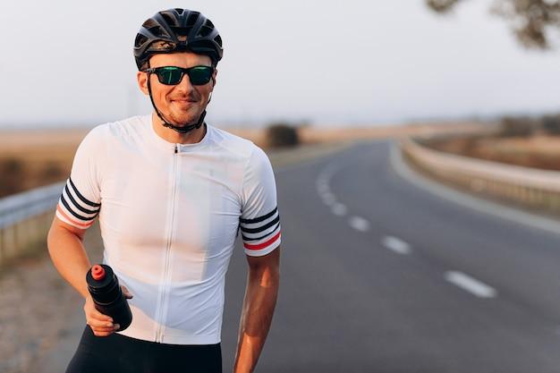 Портрет счастливого велосипедиста в очках, черном шлеме и белой футболке, держащего спортивную бутылку, позируя на асфальтовой дороге