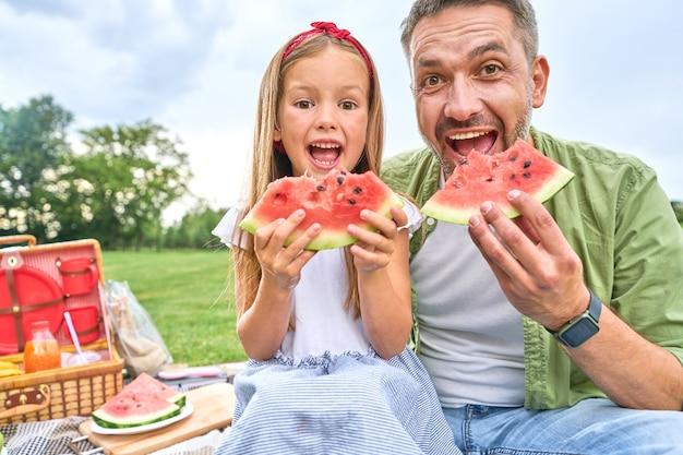 スイカを食べながらカメラを見ている幸せなお父さんと彼の愛らしい小さな娘の肖像画
