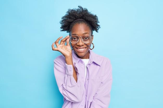 행복한 어두운 피부의 곱슬머리 여성 모델의 초상화는 이빨로 안경에 손을 얹고 카메라를 보고 만족스럽게 보입니다.