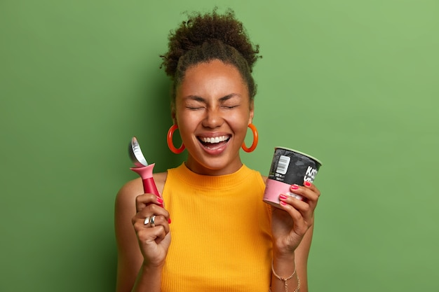 幸せな暗い肌の千年紀の女性の肖像画は、冷たい甘い冷凍アイスクリームデザートを楽しんで、スプーンを保持し、積極的に笑い、カジュアルな黄色のtシャツを着て、緑の壁に隔離された甘い歯を満足させます