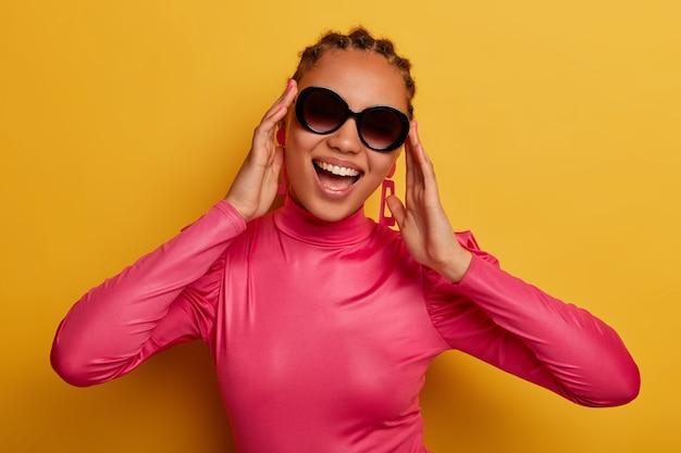 행복 한 어두운 피부 젊은 여자의 초상화는 유행 선글라스와 분홍색 스웨터를 입고, 밝은 옷을 입고 노란색 벽에 고립 된 화창한 날을 즐깁니다. 사람, 패션 및 스타일 개념.