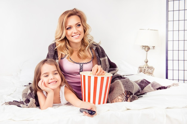 ポップコーンと漫画を見ている幸せな娘と母の肖像画