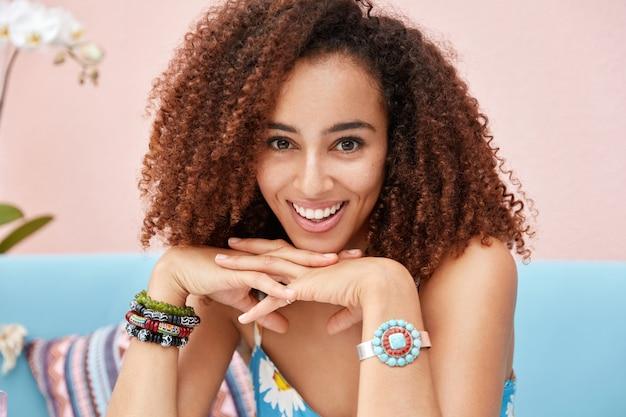 ピンクの壁に対して快適なソファーに座っていると、縮れた毛むくじゃらの髪を持つ幸せな喜んで暗い肌の混血女性の肖像画は、リラックスした感じ