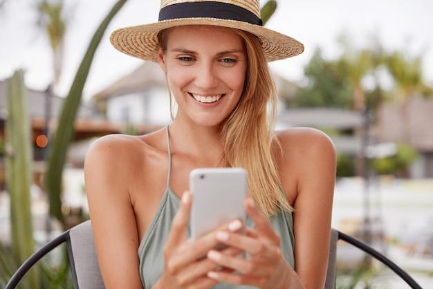 幸せな喜んでいる女性の肖像画は麦わら帽子をかぶって、陽気な表情があり、スマートフォンで何かを読み、高価な屋外カフェで自由な時間を楽しんで、夏の残りを持っています。携帯電話で笑顔の女性