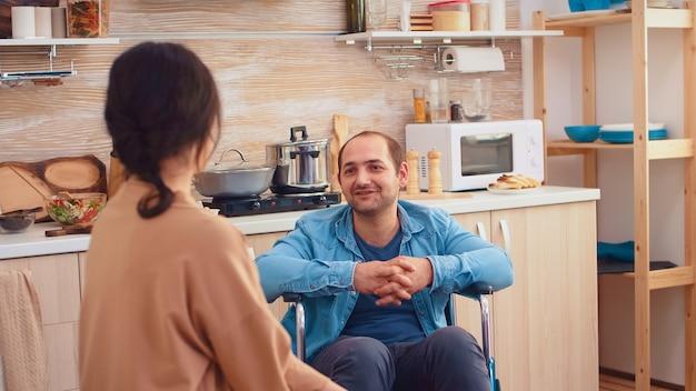 キッチンで妻を見ている車椅子の幸せな障害者の肖像画。麻痺障害者障害者愛と人間関係からの移動の助けを得ることが困難な