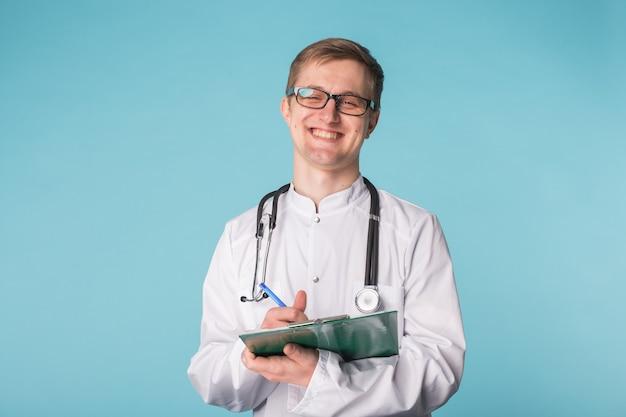 파란색 배경 클립보드에 작성 하는 행복 한 의사의 초상화