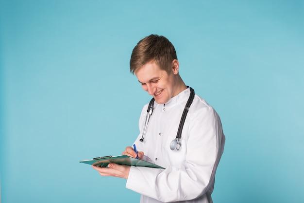 青に対してクリップボードに書く幸せな医者の肖像画