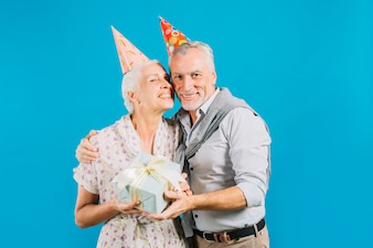 Portrait of happy elderly couple holding birthday gift on blue background