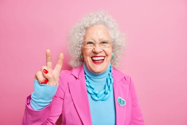 Портрет счастливой пожилой европейской женщины с вьющимися волосами делает жест мира, весело носит яркий макияж, одетый в модную одежду