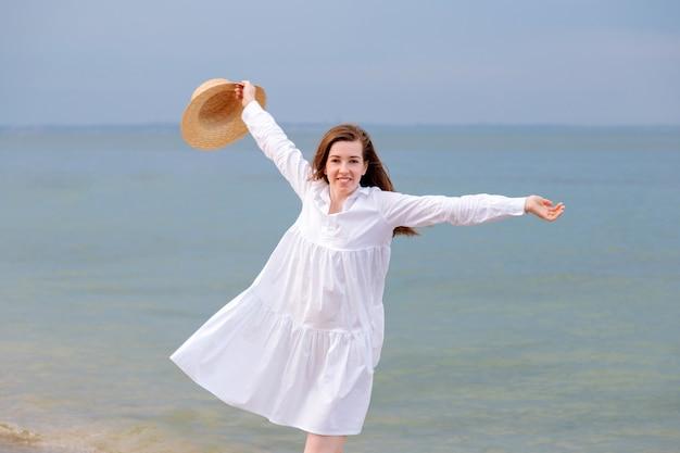海のビーチで日没で休んでいる白いドレスで若い女性を楽しんで幸せの肖像画。海岸で麦わら帽子を手に幸せな女性。