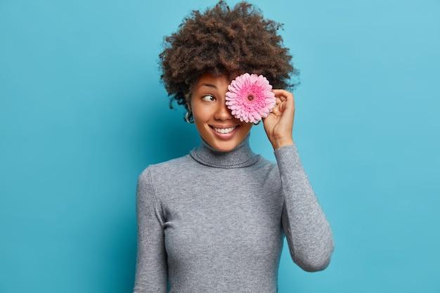 행복한 열정적 인 민족 소녀의 초상화는 곱슬 머리가 거베라 꽃으로 눈을 덮고 긍정적으로 미소 짓고 캐주얼 터틀넥을 착용합니다.