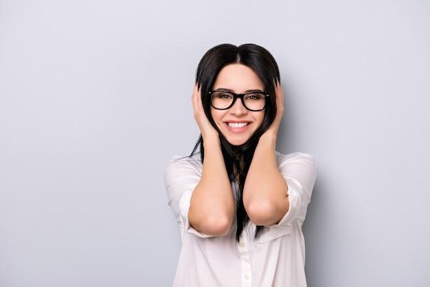 Портрет счастливой возбужденной веселой молодой женщины в очках, касающейся головы и улыбающейся, стоя на сером пространстве
