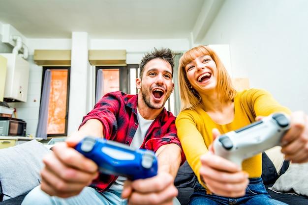 ビデオゲームをしている幸せな興奮したカップルの肖像画。