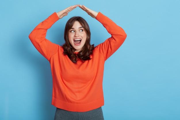 安全を感じ、家の屋根のジェスチャーの下で自信を持って、家を夢見て、口を開けて脇を見て、青い壁の上に孤立してポーズをとって、オレンジ色のセーターを着ている幸せな興奮した女の子の肖像画。
