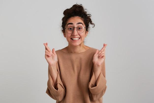 Портрет счастливой, возбужденной девушки с темным пучком вьющихся волос, в бежевом джемпере и очках