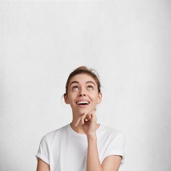 Портрет счастливой, взволнованной довольной прекрасной женщины смотрит вверх, видит что-то приятное, носит повседневную футболку, изолированную на белом фоне. люди, счастье и концепция рекламы