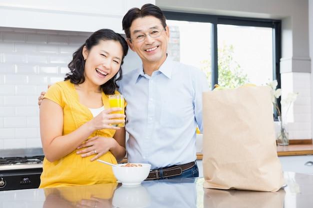 朝の台所で幸せな妊娠中のカップルの肖像画