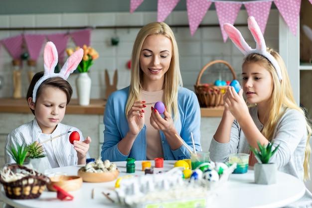 행복 한 가족의 초상화는 부활절을 준비하는 동안 토끼 귀에 입고 계란 그림입니다. 그들은 테이블에 앉아