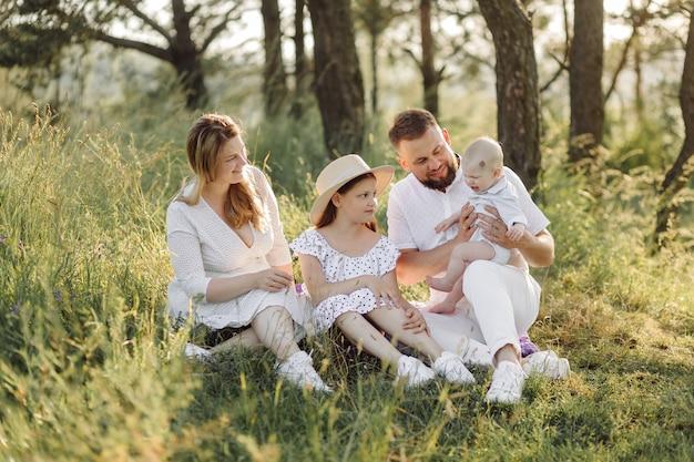 時間を過ごし、自然の中で遊ぶ日没時の幸せな家族の肖像画。