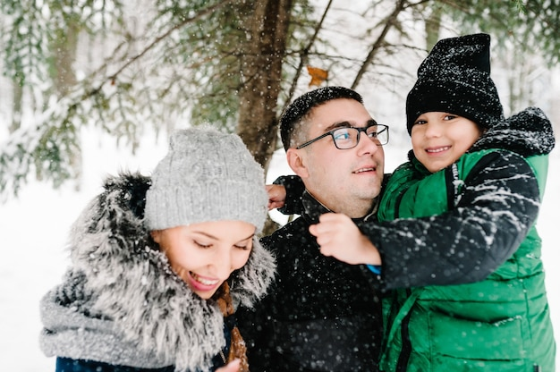冬の公園で雪を吹いて幸せな家族の肖像画。父、母、子供たちの男の子は、自然の中で雪に覆われた冬の散歩を楽しんで遊んでいます。