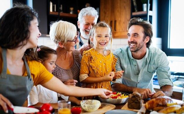 自宅のキッチンで料理をする幸せな家族の肖像画