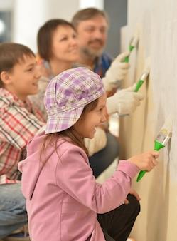家で修理し、壁を塗る幸せな家族の肖像画