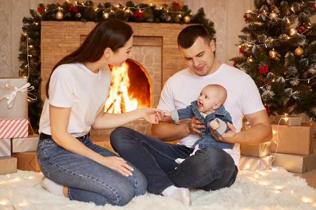 Портрет счастливой семьи, отца, матери и дочери малыша, позирующих у камина и рождественской елки у себя дома, счастливы вместе отмечать зимние праздники, с новым годом.