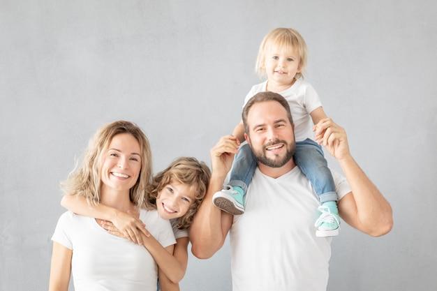 행복 한 가족의 초상화-아버지, 어머니, 딸 및 아들-회색 표면에 대하여