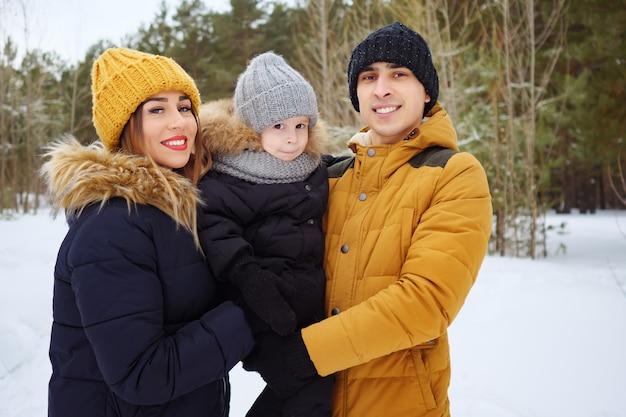 Портрет счастливой семьи в зимний день, глядя на камеру. мама и папа обнимают своего маленького сына в зимнем парке. семейные прекрасные моменты.