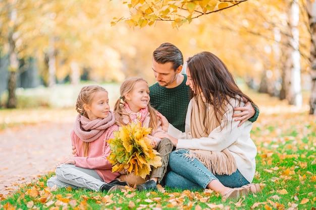 秋の日の4人の幸せな家族の肖像画