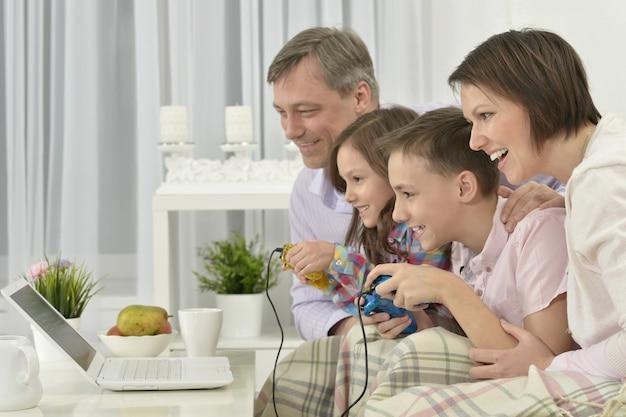 집에서 노트북을 가지고 노는 행복한 가족의 초상화