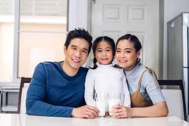 Портрет счастливой семьи позирует и пьет молоко