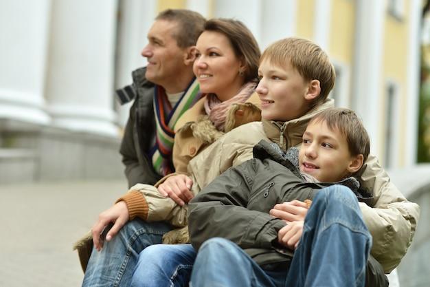 秋の公園でリラックスして幸せな家族の肖像画