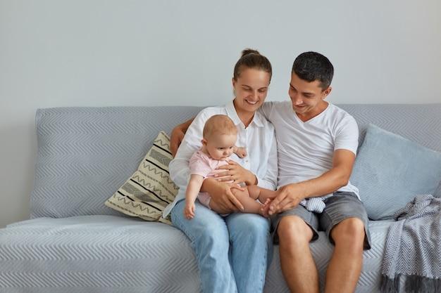 リビングルームのソファに座っている幸せな家族の肖像画、カジュアルな服を着ている人々、自宅で乳児と過ごす時間、親子関係、子供時代。