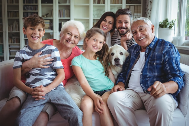 リビングルームのソファーに座っている幸せな家族の肖像画