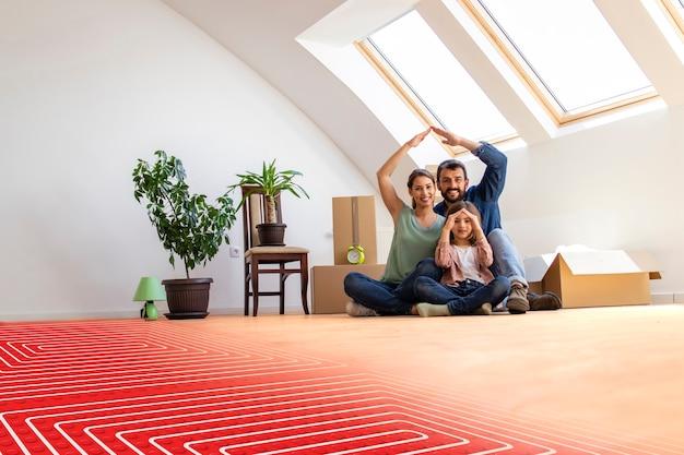 바닥 난방과 파이프가 있는 따뜻한 쪽모이 세공 마루에 앉아 있는 행복한 가족의 초상화