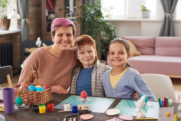 테이블에 앉아 집에서 함께 휴가를 위해 달걀을 그리는 동안 카메라를 보며 웃고 있는 행복한 가족의 초상화