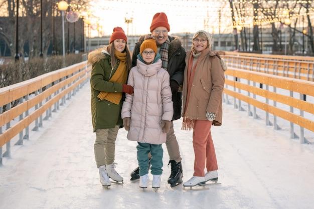 アイススケートリンクに立って一緒にスケートしながらカメラに微笑んで幸せな家族の肖像画