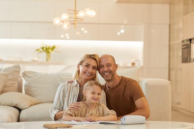 Портрет счастливой семьи улыбается, помогая милой маленькой девочке, опираясь на учебу дома