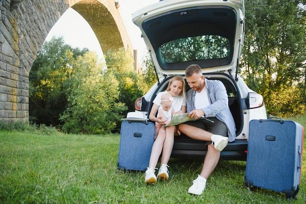 행복 한 가족의 초상화입니다. 휴가, 여행 - 여름 휴가를 위한 여행 준비가 된 가족. 가방 및 자동차 경로입니다.