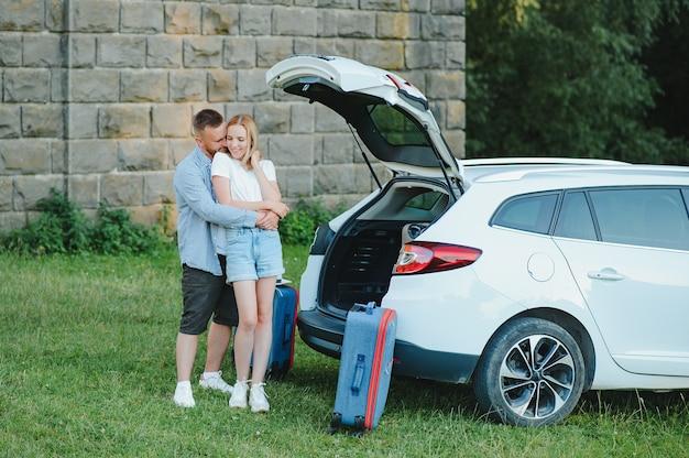 幸せな家族の肖像画。休暇、旅行-夏休みの旅行の準備ができている家族。スーツケースと車のルート。