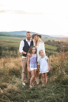 国のフィールドに立っているスタイリッシュなカウボーイ自由奔放に生きる服を着ている子供たちと幸せな家族の肖像画