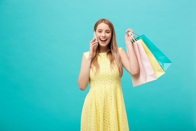 携帯電話で呼び出す買い物袋を持つ幸せなファッション白人女性の肖像画。青い背景で隔離。