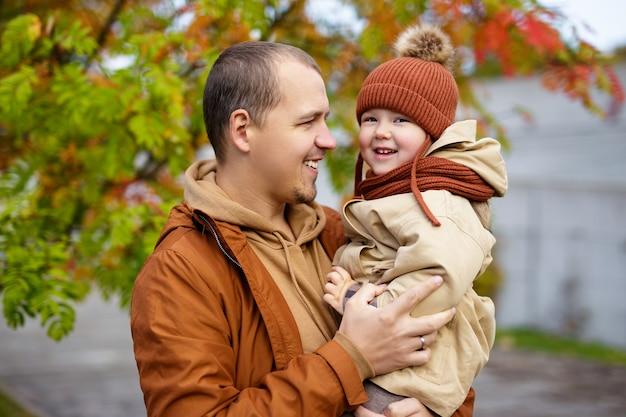 Портрет счастливого отца и милой маленькой дочери в осеннем парке