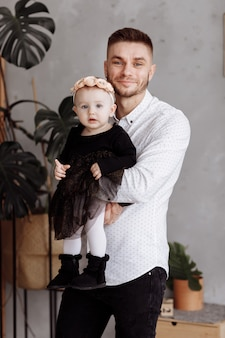 幸せな父と自宅で彼の手に彼の愛らしい小さな娘の肖像画。幸せな子供時代。お父さんは赤ちゃんの女性を愛で抱いています。家族の一見。
