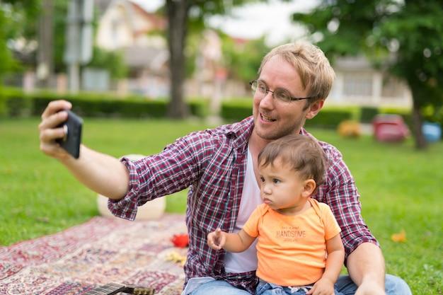 幸せな父と屋外で一緒に結合する多民族の赤ちゃんの息子の肖像画