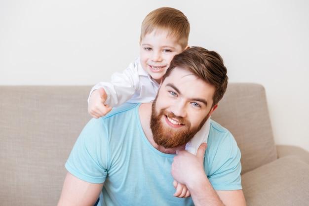 一緒に自宅のソファに座っている幸せな父と息子の肖像画