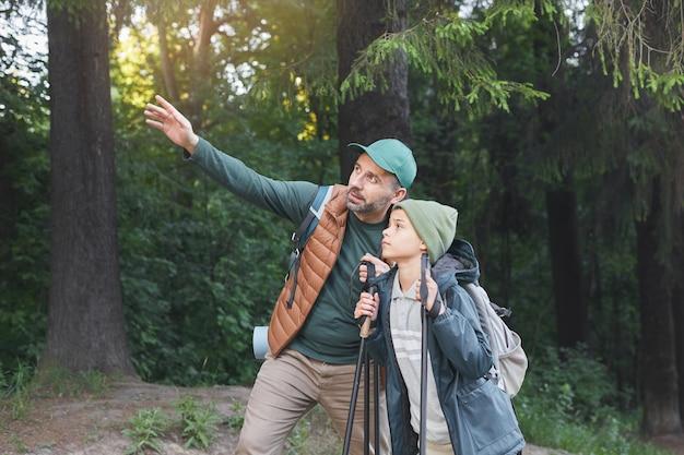 一緒にハイキングや森の中を歩きながら自分撮りをしている幸せな父と息子の肖像画、コピースペース